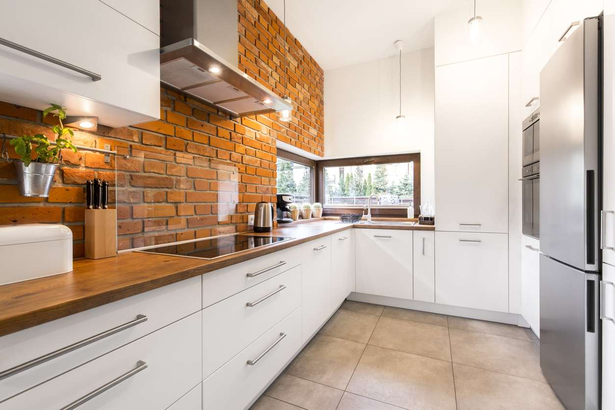 Brick wall in spacious modern designed white kitchen with marble floor
