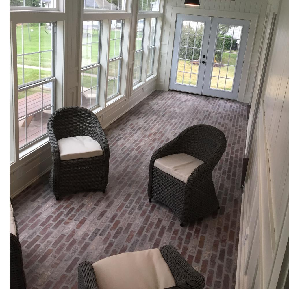 Sunroom with a brick floor